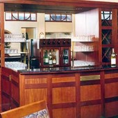 Bar, built-in: glass, granite, mirror, stained mahogany and natural anigre.