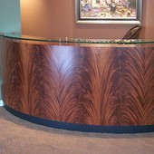 "Reception desk:  ""Barked"" glass with stainless steel pylons, stained crotch maho"